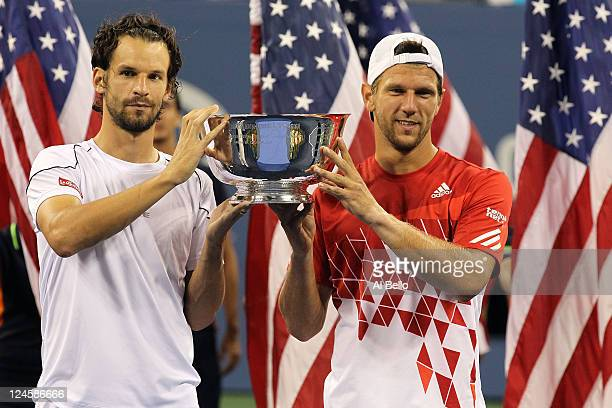 Jurgen Melzer of Austria and Philipp Petzschner of Germany celebrate with the winner's trophy after they defeated Mariusz Fyrstenberg of Poland and...