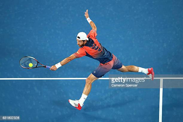 Jurgen Melzer of Austria plays a backhand in his first round match against Roger Federer of Switzerland on day one of the 2017 Australian Open at...