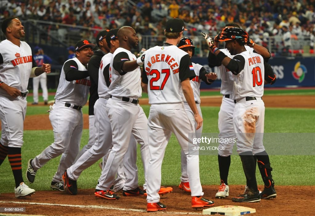 Jurickson Profar (R) of the Netherlands celebrates with teammates after their victory against Taiwan in their first round game of the World Baseball Classic at Gocheok Sky Dome in Seoul on March 8, 2017. / AFP PHOTO / JUNG Yeon-Je