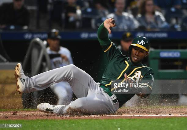 Jurickson Profar of the Oakland Athletics slides into home plate to score a run in the second inning during the game against the Pittsburgh Pirates...