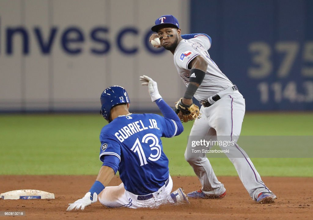 Jurickson Profar #19 of the Texas Rangers gets the force out of Lourdes Gurriel Jr. #13 of the Toronto Blue Jays but cannot turn the double play in the sixth inning during MLB game action at Rogers Centre on April 29, 2018 in Toronto, Canada.