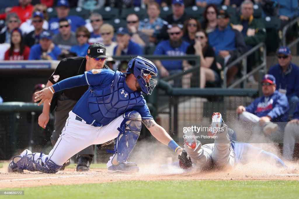 Jurickson Profar #19 of the Texas Rangers safely slides into home plate to score a run past catcher Cam Gallagher #36 of the Kansas City Royals during the second inning of the spring training game at Surprise Stadium on February 26, 2017 in Surprise, Arizona.