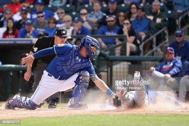 Jurickson Profar of the Texas Rangers safely slides into home plate to score a run past catcher Cam Gallagher of the Kansas City Royals during the...