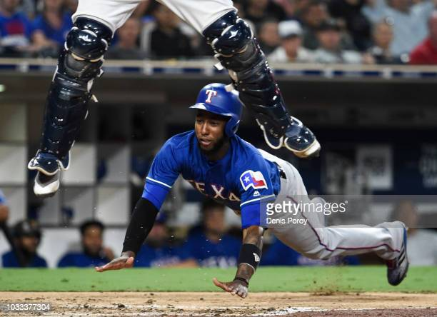 Jurickson Profar of the Texas Rangers scores as Francisco Mejia of the San Diego Padres jumps for a high throw during the fifth inning of a baseball...