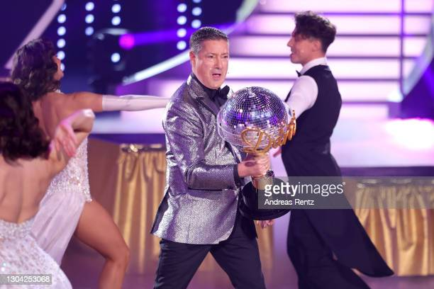"""Juror Joachim Llambi holds the trophy on stage during the pre-show """"Wer tanzt mit wem? Die grosse Kennenlernshow"""" of the television competition..."""