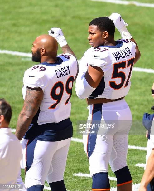 Jurrell Casey and DeMarcus Walker of the Denver Broncos raise their hands during the National Anthem prior to the game abasing the Pittsburgh...