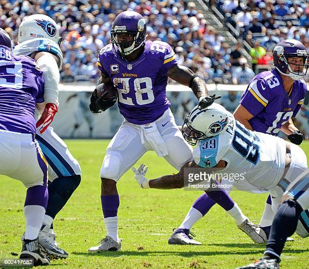 Jurrell Casey of the Tennessee Titans tackles Adrian Peterson of the Minnesota Vikings in the backfield during the first half at Nissan Stadium on...