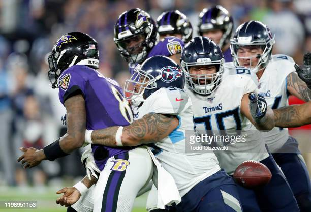 Jurrell Casey of the Tennessee Titans tackles quarterback Lamar Jackson of the Baltimore Ravens to cause a fumble during the AFC Divisional Playoff...