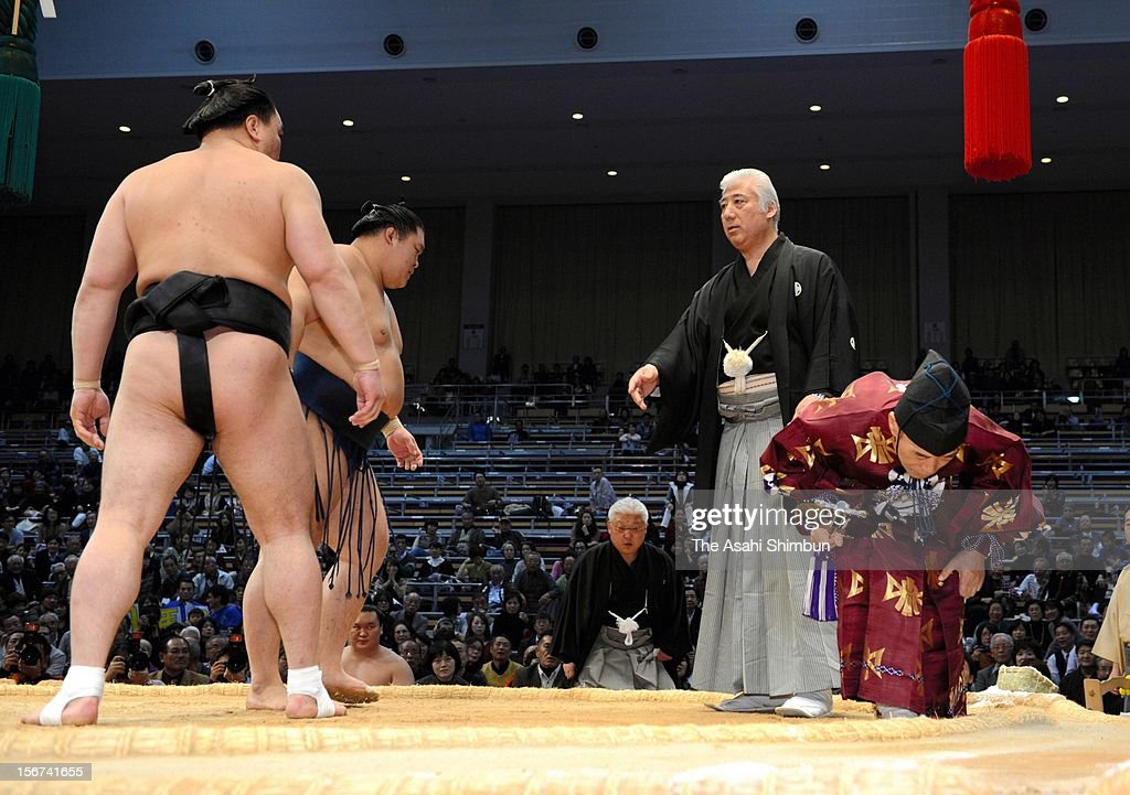 A jury (2R) intervenes while gyoji (referee) Shikimori Inosuke (1R) checks if a footprint was left outside the ring, at the bout between yokozuna Harumafuji (1L) and Goeido (2L), during day nine of the Grand Sumo November Tournament at Fukuoka Convention Center on November 19, 2012 in Fukuoka, Japan. After discussion by juries, the meet went on rematch and Harumafuji won.