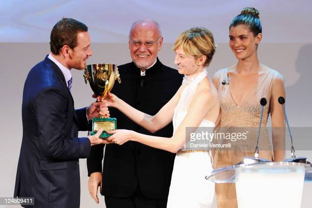 Jury member actress Alba Rohrwacher presents Actor Michael Fassbender of 'Shame' the Coppa Volpi for Best Actor as festival director Marco Muller and...