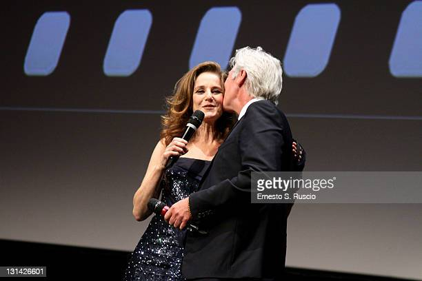 Jury member Debra Winger receives a kiss from actor Richard Gere as he accepts his Marc' Aurelio award for Lifetime Achievement during the Closing...