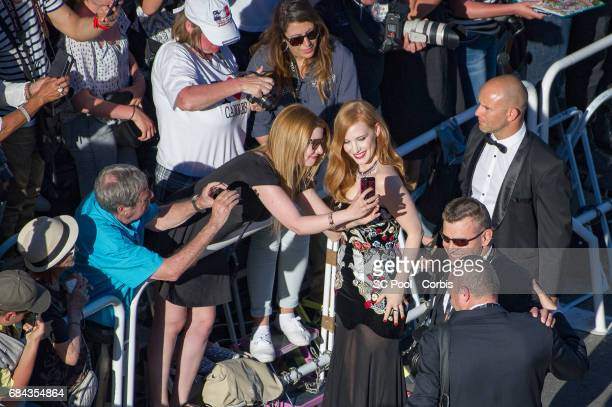 Jury member Jessica Chastain poses for selfies with fans as she attends the Ismael's Ghosts screening and Opening Gala during the 70th annual Cannes...