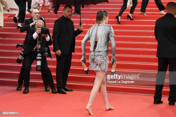 Jury member Kristen Stewart takes off her shoes as she walk the red carpet for the screening of 'Blackkklansman' during the 71st annual Cannes Film...