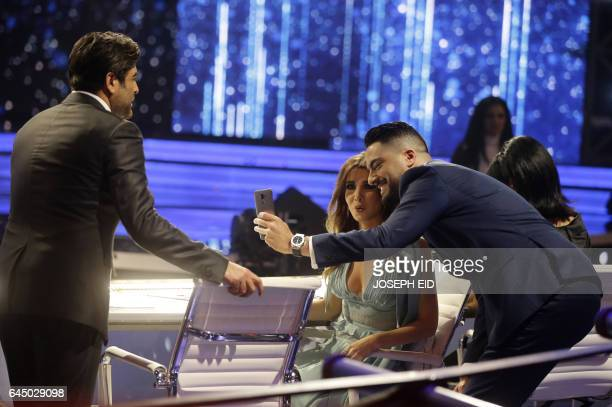 Jury members and Arab singing stars Wael Kfoury Nancy Ajram and Hassan alShafei share a light moment during a break in the last show before the final...