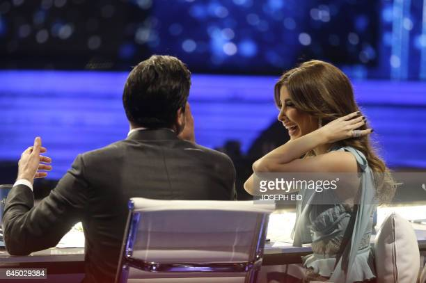 CORRECTION Jury members and Lebanese singing stars Nancy Ajram and Wael Kfoury share a laugh during a break in the last show before the final in the...
