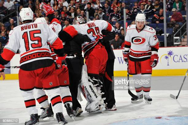 Jussi Jokinen looks down at a pool of blood as goaltender Cam Ward both of the Carolina Hurricanes is helped off of the ice after suffering a...