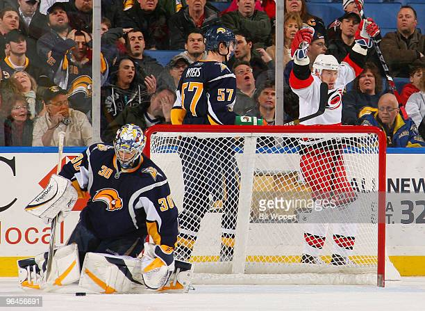 Jussi Jokinen of the Carolina Hurricanes celebrates his game winning goal late in the third period in front of Ryan Miller and Tyler Myers of the...