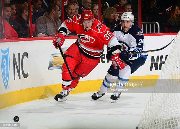 Jussi Jokinen of the Carolina Hurricanes chases the puck behind the net as Grant Clitsom of the Winnipeg Jets defends during an NHL game on February...