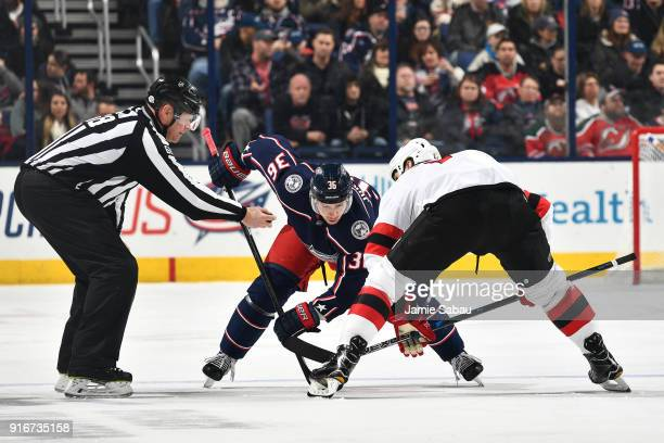 Jussi Jokinen of the Columbus Blue Jackets and Brian Boyle of the New Jersey Devils await the drop of the puck from linesmen Scott Driscoll during...