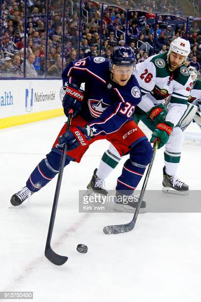 Jussi Jokinen of the Columbus Blue Jackets and Daniel Winnik of the Minnesota Wild battle for control of the puck during the game on January 30 2018...
