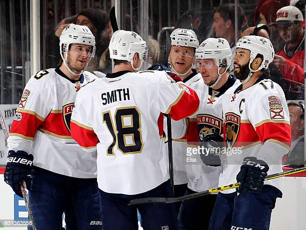 Jussi Jokinen of the Florida Panthers is congratulated by teammates Mark PysykReilly Smith and Derek MacKenzie after Jokinen scored an empty net goal...