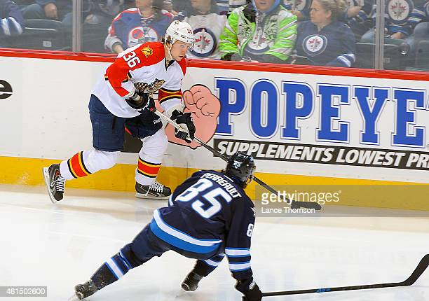 Jussi Jokinen of the Florida Panthers plays the puck along the boards as Mathieu Perreault of the Winnipeg Jets defends during second period action...