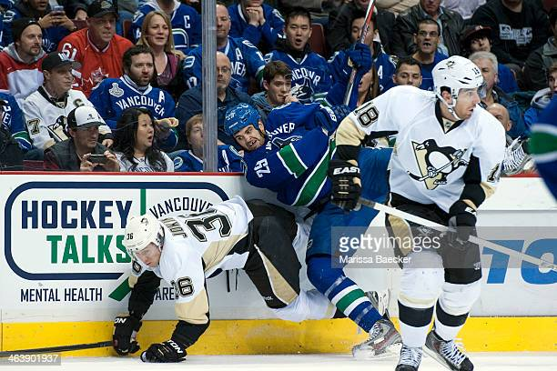 Jussi Jokinen of the Pittsburgh Penguins falls to the ice after being checked by Tom Sestito of the Vancouver Canucks on January 7, 2014 at Rogers...