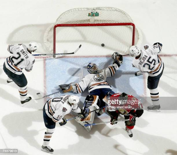 Jussi Markkanen of the Edmonton Oilers lies spread eagle on the ice with the puck in the net behind him as teammates Jason Smith;Jan Hejda and Shawn...