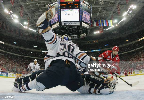 Jussi Markkanen of the Edmonton Oilers makes a save against Mark Recchi of the Carolina Hurricanes during game seven of the 2006 NHL Stanley Cup...