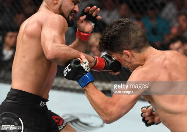 Jussier Formiga of Brazil punches Joseph Benavidez in their flyweight bout during the UFC Fight Night event at the Target Center on June 29, 2019 in...