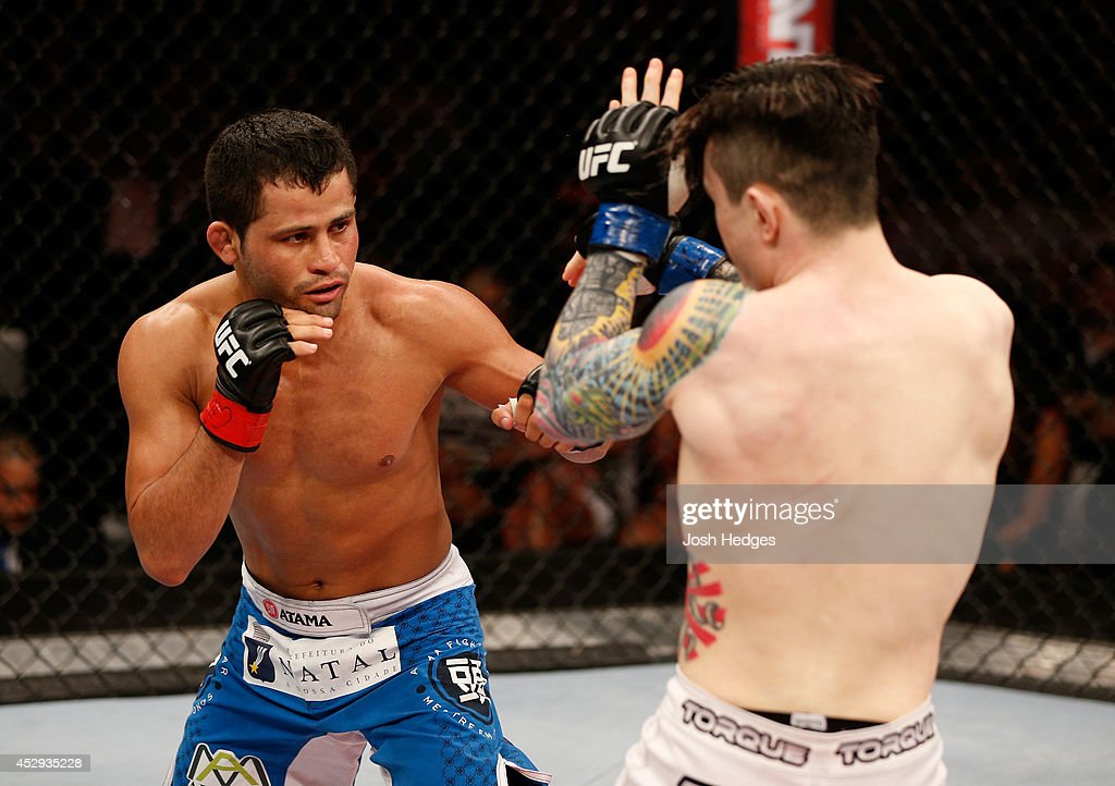 Jussier Formiga punches Scott Jorgensen in their flyweight bout during the UFC Fight Night event at Ginasio Nelio Dias on March 23, 2014 in Natal, Brazil.