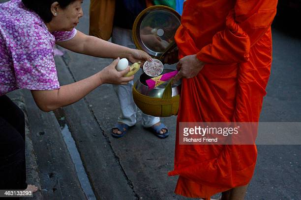 Just after dawn a Thai lady gives alms to a Buddhist monk in downtown Bangkok.