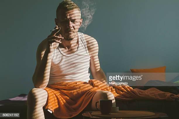お目覚めのイマイチ男性喫煙タバコの最初の朝