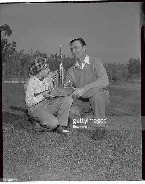 Just before shooting a practice round at Riviera Country Club, Dec. 31, Ben Hogan presents the Los Angeles Open Mascot trophy to 12-year-old Bill...