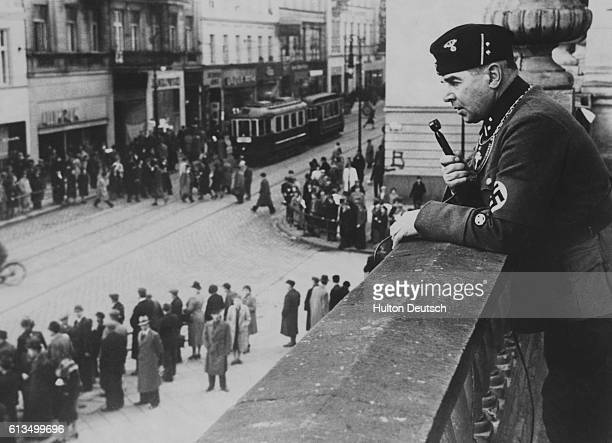 Just days after the German takeover of Poland a Nazi policeman regulates pedestrian traffic on a street in Posen by speaking commands into a...