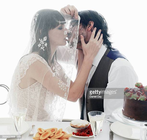Just married couple kissing under veil at table