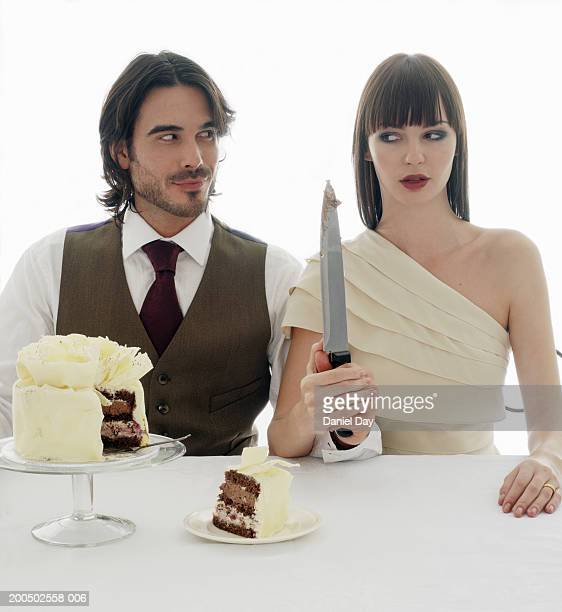 Just married couple looking at each other while cutting wedding cake at reception