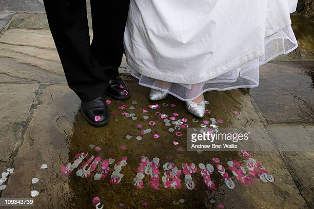 just married in confetti by bride & groom's shoes