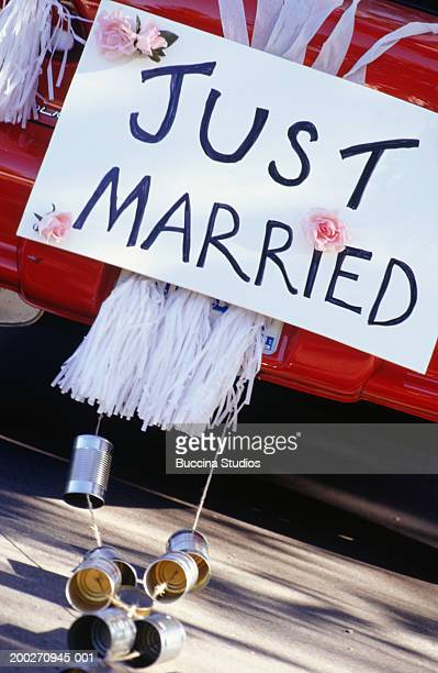 Just married sign and empty cans fastened to car