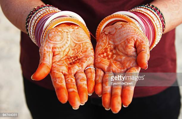 Just married woman is showing her traditional henna paintings on her hands on December 13 2009 in Kovalam Beach near Trivandrum India Arranged...