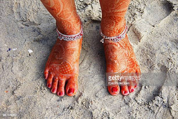 Just married woman is showing her traditional henna paintings on her feet on December 13, 2009 in Kovalam Beach near Trivandrum, India. Arranged...