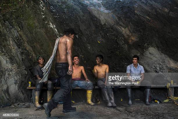 Just outside the Minería Texas Colombia plant emerald miners play Tejo a popular Colombian game where players throw a 'tejo' or rock to a target on...
