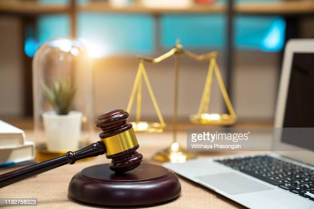 justice and law concept.lawyer workplace with laptop and documents with dark wooden - law office stock photos and pictures