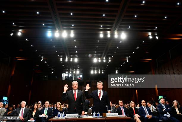 Justice Department Inspector General Michael Horowitz and FBI Director Christopher Wray take an oath before testifying to the Senate Judiciary...