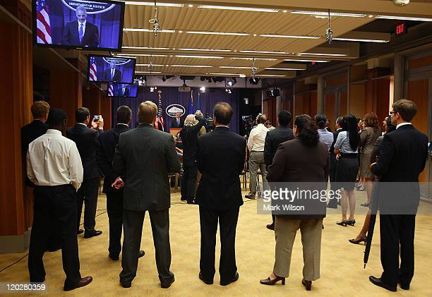 Justice Department staffers watch as Attorney General Eric Holder speaks about an international child pronography in investigation during a news...