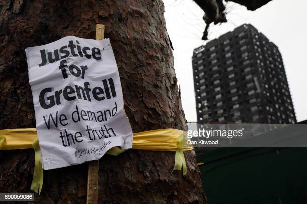A 'Justice for Grenfell' sign hangs on a tree near Grenfell Tower on December 11 2017 in London England An inquiry into the Grenfell Tower fire was...