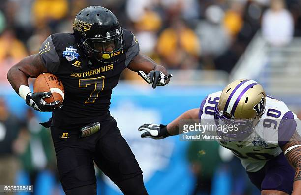 Justice Hayes of the Southern Miss Golden Eagles runs the ball against Taniela Tupou of the Washington Huskies during the Zaxby's Heart of Dallas...