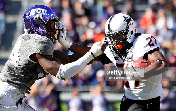 Justice Hill of the Oklahoma State Cowboys carries the ball against Josh Carraway of the TCU Horned Frogs in the second half at Amon G Carter Stadium...