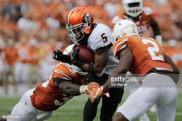 Justice Hill of the Oklahoma State Cowboys is tackled by Gary Johnson of the Texas Longhorns and Kris Boyd in the fourth quarter of the Texas...