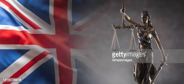justice is blind statue symbolizing law and legal system with united kingdom of great britain nad northern ireland flag in the background. - brexit stock pictures, royalty-free photos & images
